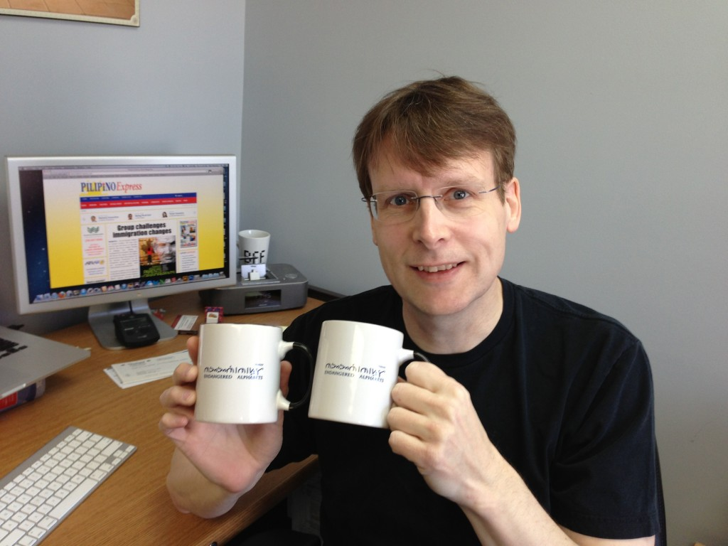 Paul Morrow with the Endangered Mug, featuring his own text in Baybayin.